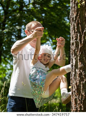 Young father and his happy little daughter playing in a summer park - stock photo