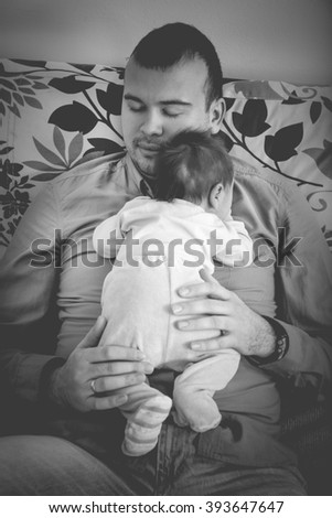 Young Father and His Little Baby Boy Together. Papa with His Cheerful Newborn on Sofa Taking Good Time. Domestic Family. Closeup Portrait of Dad and His Daughter Relaxing on Bed at Home Caring for Her - stock photo