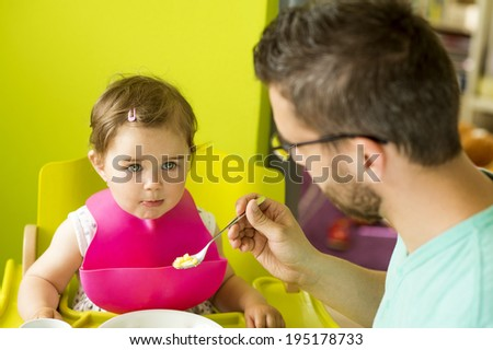 Young father and his little daughter having breakfast together - stock photo