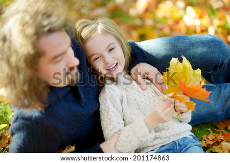 Young father and his little daughter sitting on yellow maple leaves on beautiful sunny autumn day - stock photo