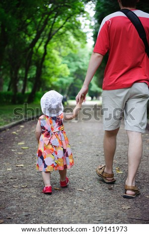 Young father and his little daughter walking in the park - stock photo