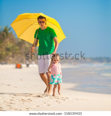 Young father and his little daughter walking under a yellow umbrella on white sand beach - stock photo