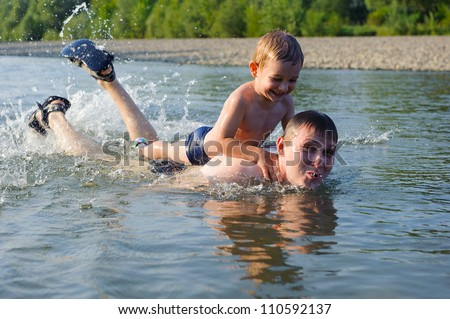 Young father and his little son swimming in river - stock photo