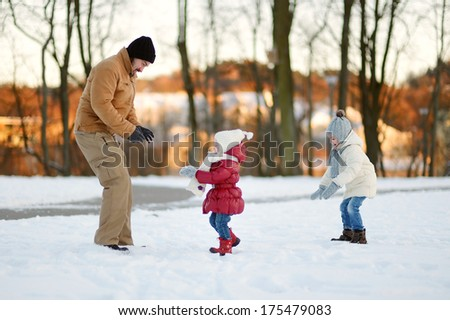 Young father and his two daughters having fun on winter day - stock photo