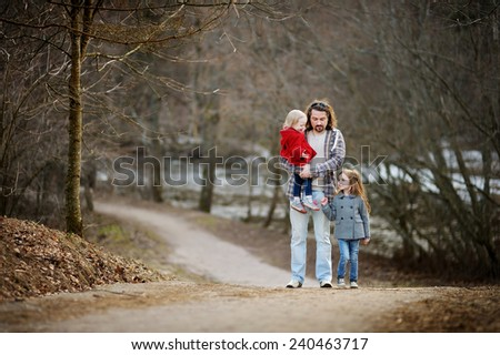 Young father and his two little daughters on beautiful spring day outdoors - stock photo