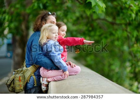 Young father and his two little daughters on warm and sunny summer evening - stock photo