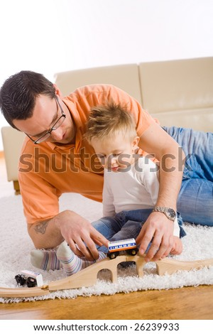 Young father and little baby boy playing together with toy train at home. - stock photo