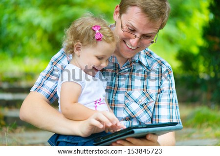 Young father and little  cute daughter reading in summer park - stock photo