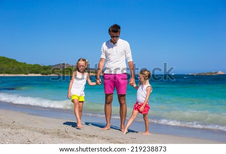 Young father and little girls have fun during tropical vacation - stock photo