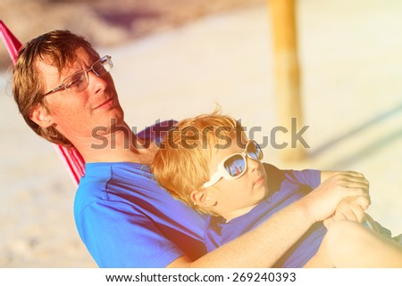 Young father and little son relaxing in hammock on the beach - stock photo