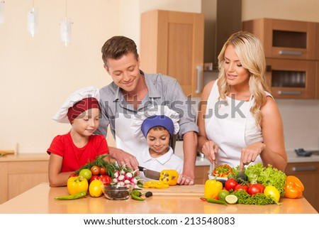 Young father and mother preparing salad together. boy and girl helping with food at kitchen - stock photo