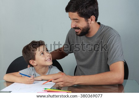 Young father and son drawing with colored pencils on the living room table - stock photo