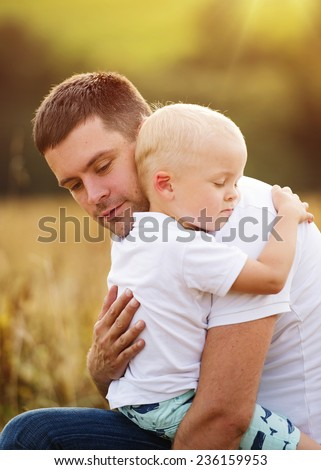 Young father and son enjoying life together. They are hugging outside in nature - stock photo