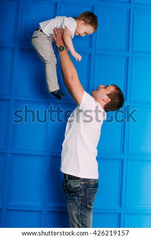 Young father and son playing together portrait. Studio shot. - stock photo
