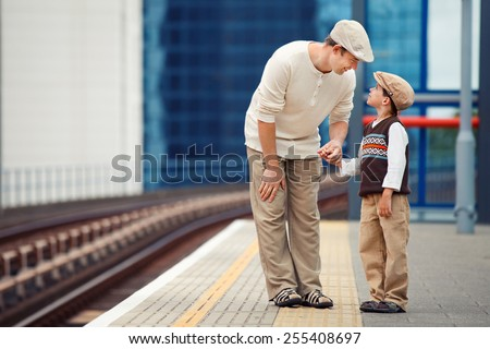 Young father and son waiting for train on railway station platform - stock photo
