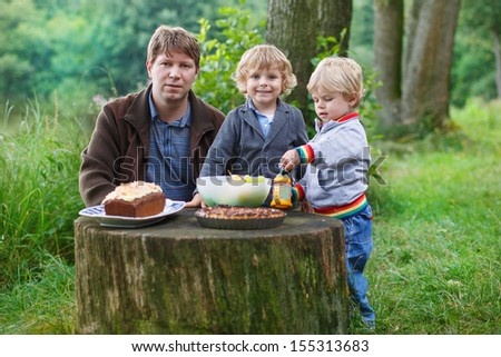 Young father and two little boys picnicking in nature forest near lake in summer - stock photo