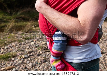 Young father carrying a baby girl in a carrier sling - stock photo