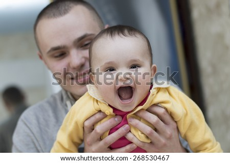 Young father holding and hugging in his arms child baby kid girl smilling laughing - stock photo