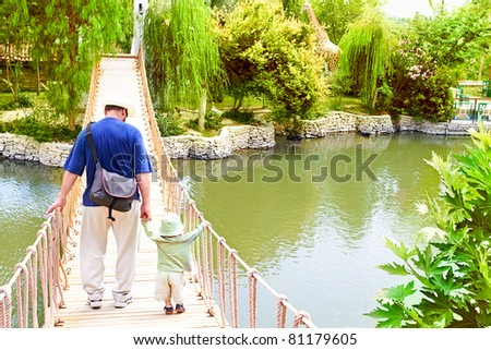 Young father holding hands with small toddler son as he teaches him to balance and walk on the bridge over lake in Park in Turkey - stock photo