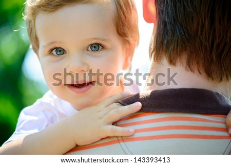 Young father holding his little son. Rear view - stock photo