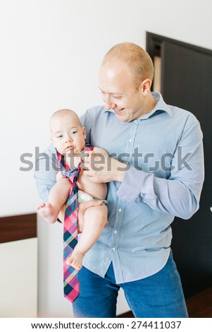 Young father holding his naked baby wearing a tie in arms - stock photo