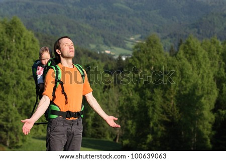 Young father is hiking with 1 year old son in baby carrier - stock photo