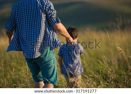 Young father is walking with his son on a field. Back view - stock photo