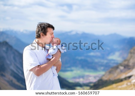 Young father kissing his newborn baby son while trekking in the beautiful Alps mountains - stock photo