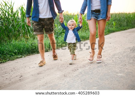 Young father, mother cute baby walking nature road near cornfield holding hands in summer - stock photo