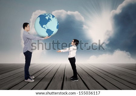 Young father passing the earth to his son - stock photo