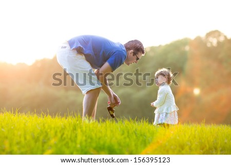 Young father playing with his baby daughter in a field on a sunny autumn evening - stock photo