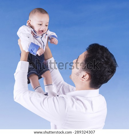 Young father playing with his baby outside and lift up the baby under blue sky - stock photo