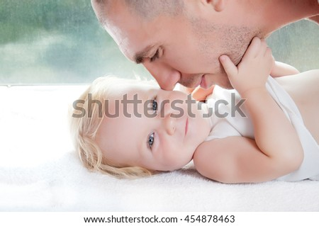 Young father playing with his cute baby in home. Pastel background. - stock photo