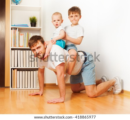 Young father playing with his two sons - stock photo