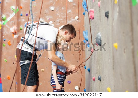 young father preparing his little son for climbing in indoor gym - stock photo