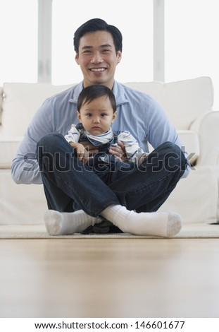 Young father sitting on floor with baby - stock photo