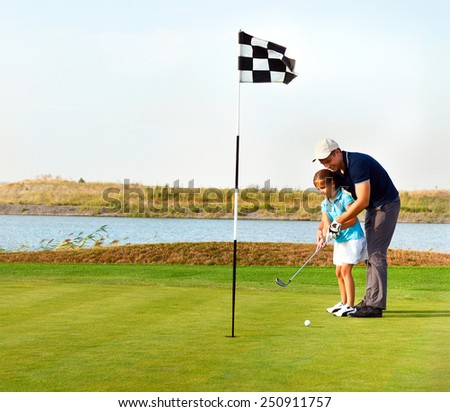 Young father teaching daughter to play golf on putting on green - stock photo