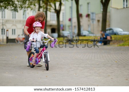 Young father teaching his daughter to ride a bicycle - stock photo