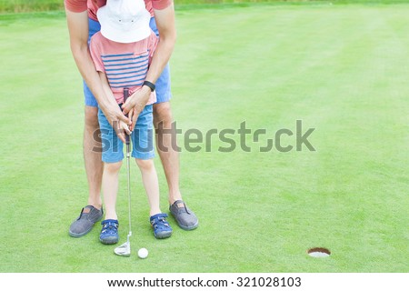 young father teaching his little son to play golf, no faces visible - stock photo
