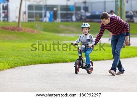 young father teaching his smiling son how to ride a bike - stock photo