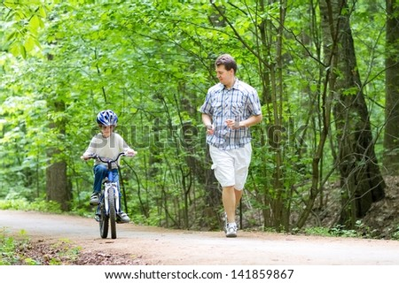 Young father teaching his son to ride a bike - stock photo