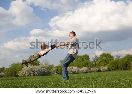 Young father twirling his little son in park - stock photo