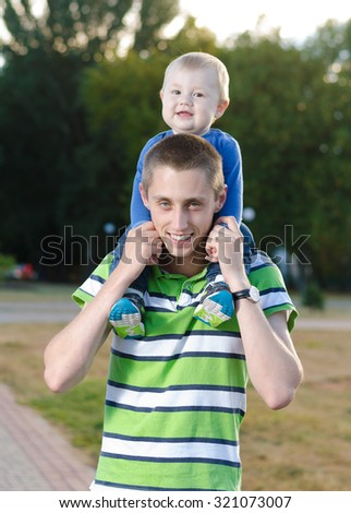 young father with a baby on his neck walks in the park - stock photo