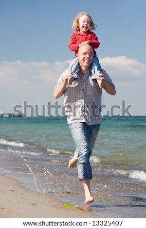 Young father with his daughter running at the beach - stock photo