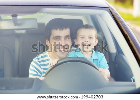 Young father with his little son driving car together - stock photo