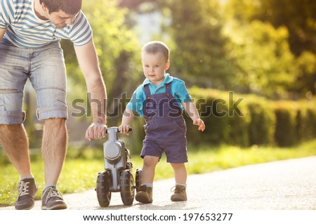 Young father with his little son on motorbike in green sunny park - stock photo