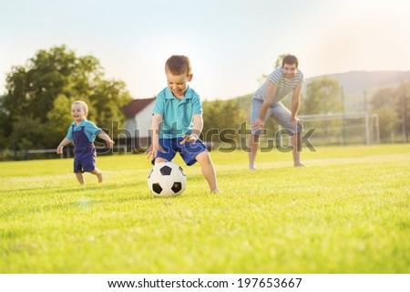 Young father with his little sons playing football on football pitch - stock photo