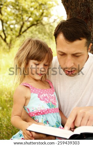 Young father with his son reading the Bible - stock photo