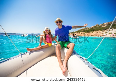 Young father with little girl resting on a big boat - stock photo