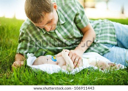 Young father with son outdoors in park, soft focus (focus on eyes of baby) - stock photo